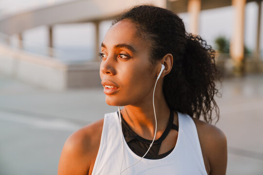Black sportswoman listening music while working out on parking