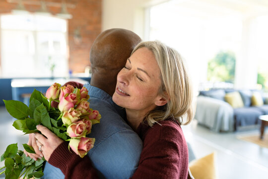 Happy senior diverse couple in living room embracing, holding flowers
