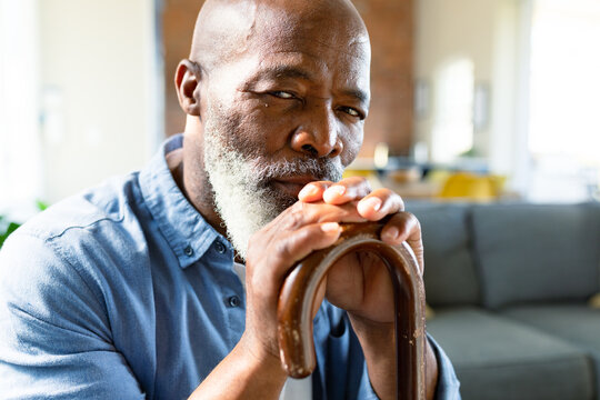 Portrait of thoughtful senior african american man in living room holding walking cane