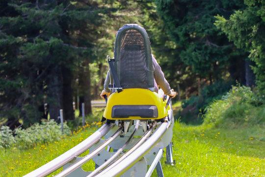 Young girl enjoying a summer fun roller alpine coaster ride