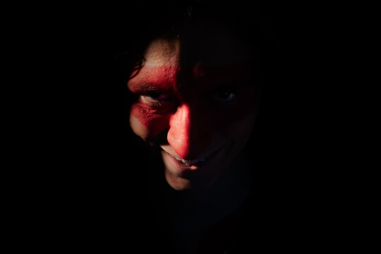 Young teenager boy with painted face on black for Halloween party
