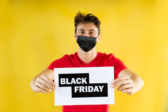 Teenager boy holding Black Friday  sale card. Special promo with yellow background.