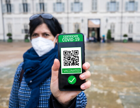 Young woman holding smartphone with qr code confirm vaccination coronavirus covid-19. Vaccine done with digital green pass passport