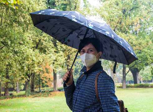 Young woman holding humbrella in a park during rainy day