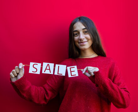 Teenager holding sale sign card with Christmas mood and red background. Sales Promotion advertising concept