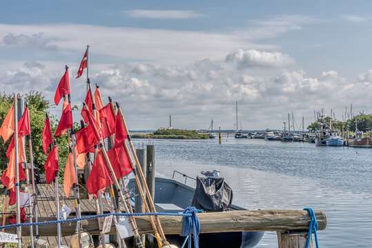 red net flags on a jetty next to a fishing boat