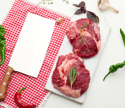 raw piece of beef ribeye with rosemary, thyme on a white table, top view