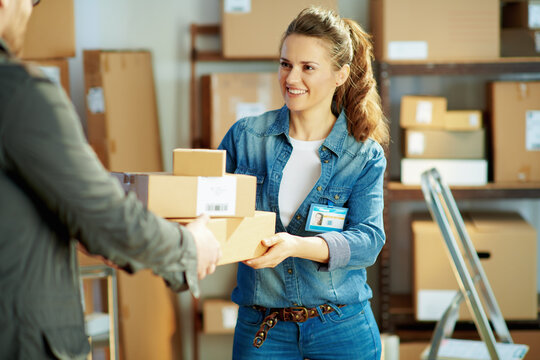 smiling young female in jeans in office giving parcel