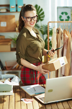 happy business owner woman using smartphone in office