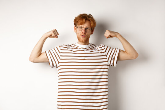Image of confident and strong redhead man flexing biceps, showing muscles after gym, standing over white background