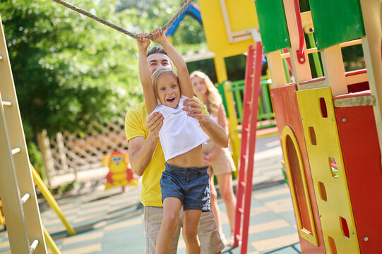Dad and daughter actively spending time on playground