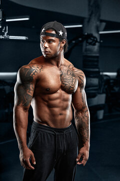 Strong and muscular afro-american man trains on modern equipment in gym. Portrait of muscular pumped up fitness trainer