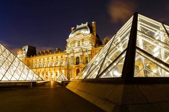 Paris, France - July 25, 2016: Night scene of lit Louvre Pyramids. Louvre is the most famous art museum in France.