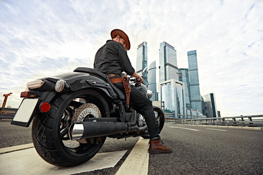 Portrait of stylish male dressed in a black leather jacket and bandana with gun sitting on his custom-made retro motorcycle, looking away, buildings of the big city on background.
