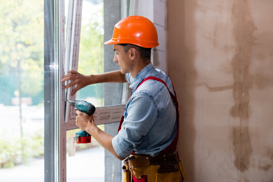 Man worker mounting window in a renovated building