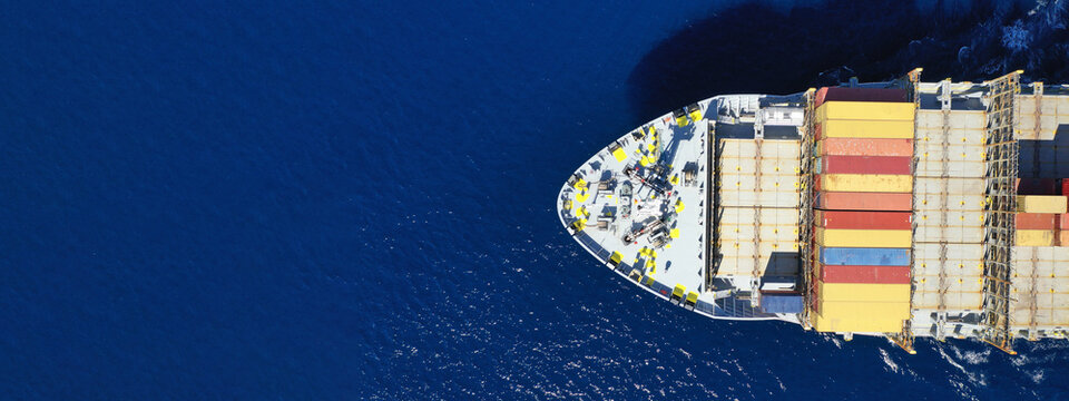 Aerial drone ultra wide panoramic view above huge colourful container carrier vessel cruising deep blue open ocean sea