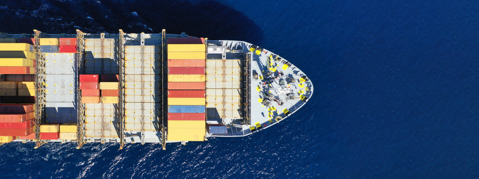 Aerial drone ultra wide top down photo of container cargo tanker ship carrying truck-size colourful containers in deep blue open ocean sea