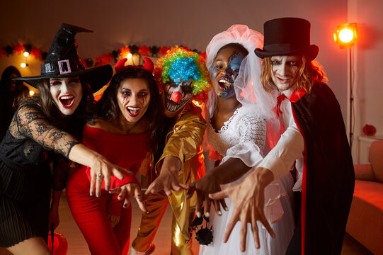 Group of adult friends having fun at dark carnival party. Happy people dressed up in spooky Halloween costumes of witch, devil, clown, corpse bride and vampire standing together and looking at camera