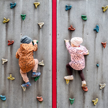 Small children climbing a rock wall at playground
