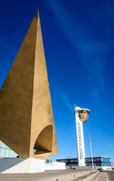 """Le Havre, France - June 12, 2021: Control tower and harbor master's office next to """"Le Signal"""" monumental sculpture by Henri-Georges Adam. The text on the tower reads """"Le Havre Gateway of Europe""""."""