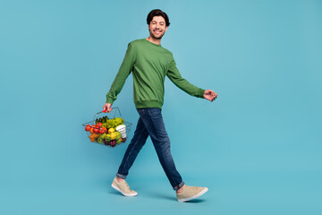 Fototapeta Full size profile side photo of smiling guy go walk with groceries buy purchase products isolated on blue color background obraz
