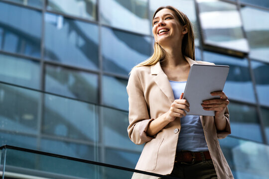 Portrait of a successful business woman using digital tablet in front of modern business building