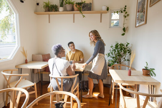 Cheerful cafe owner talking to customers