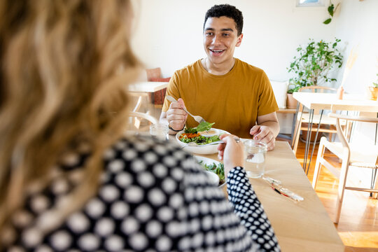 Cheerful young man enjoying lunch with friend at cafe