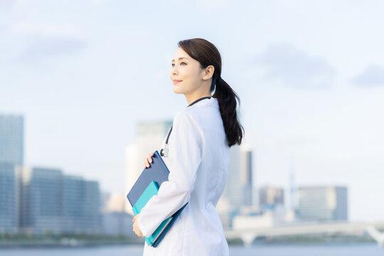 都市の前に立つ白衣の女性 医師 科学者