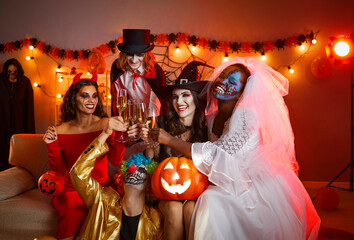 Fototapeta Group of cheerful friends in spooky halloween costumes posing with glasses of champagne in hands. Multiethnic young people celebrate Halloween at home in room with holiday decorations and red lights. obraz
