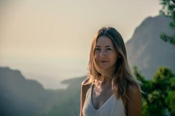 Fototapeta kobieta o wschodzie słońca na tle gór obraz