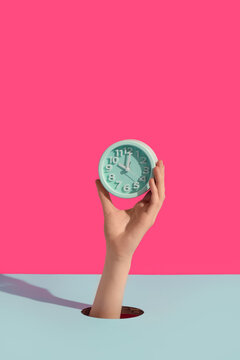 Female hands holding alarm clock through hole on color background
