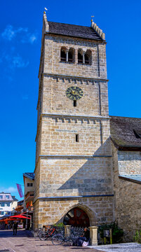 tower of the parish church Saint Hippolyt with beggar woman in the foreground at Zell on the lake, Austria