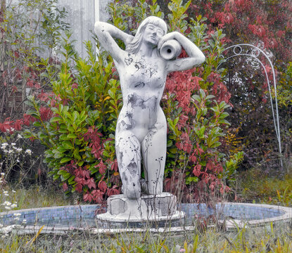 desolate well with figure of a naked woman at a fore yard in autumn, Austria