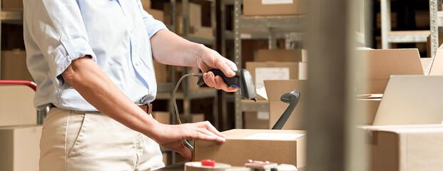 Fototapeta Mature female online store business owner scanning parcel shipping box. obraz
