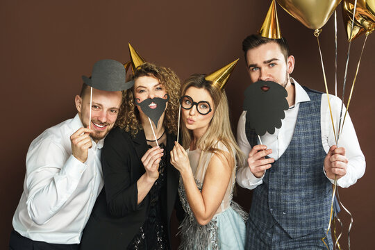 Happy people wearing party hats with photo booth props are celebrating holiday or event