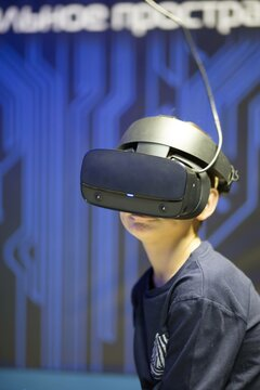boy in virtual reality glasses playing on the background of the monitor