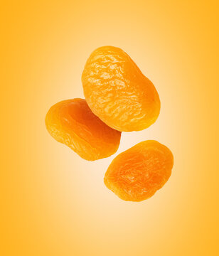 Dried apricots close up in the air on a yellow background