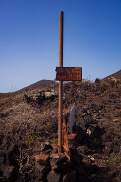 View of an old rusty signage on the lava hill, Linosa
