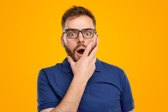 Shocked man with hands on yellow background