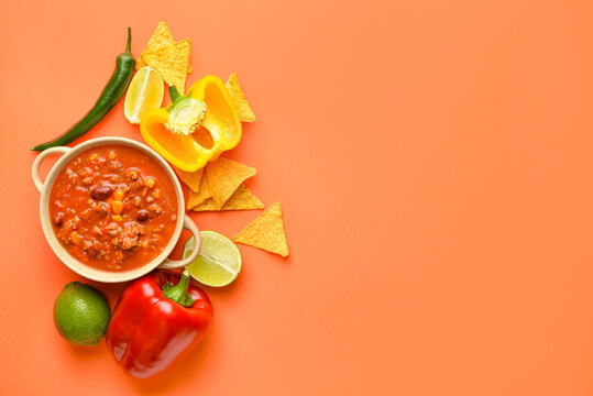 Bowl with chili con carne, ingredients and nachos on color background