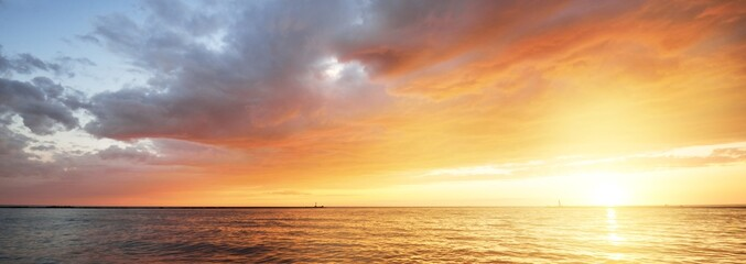 Fototapeta Baltic sea at sunset. Dramatic sky with glowing golden pink clouds, reflections in the water. Lighthouse. Setting sun. Epic seascape. Abstract natural pattern, texture, background, concept image obraz