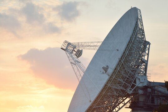 Large radio telescope. Dramatic sunset sky, glowing clouds. Nature, weather, science, equipment, technology, international security, communications, remote places