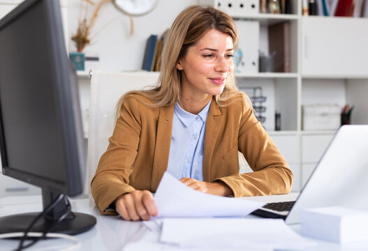 Successful adult business woman using laptop at workplace