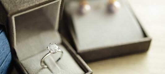Fototapeta Diamond ring in jewelry gift box on wood table obraz