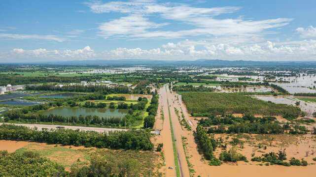 Aerial view of Flooded the village and Country road with car, View from above shot by drone