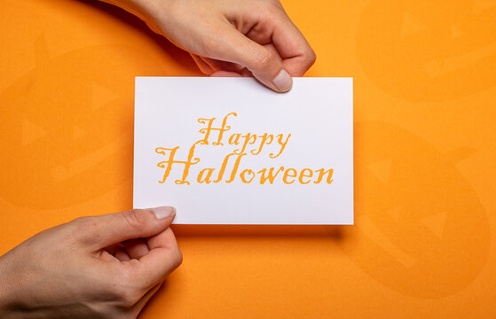 female hands holding a piece of paper with the inscription happy halloween in orange writing over orange background cardboard