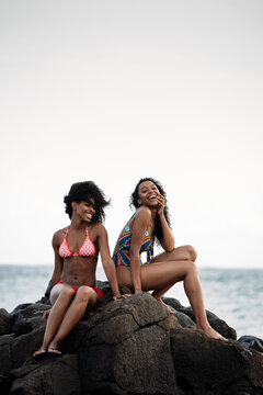 Two sisters sitting in rocks by the seashore