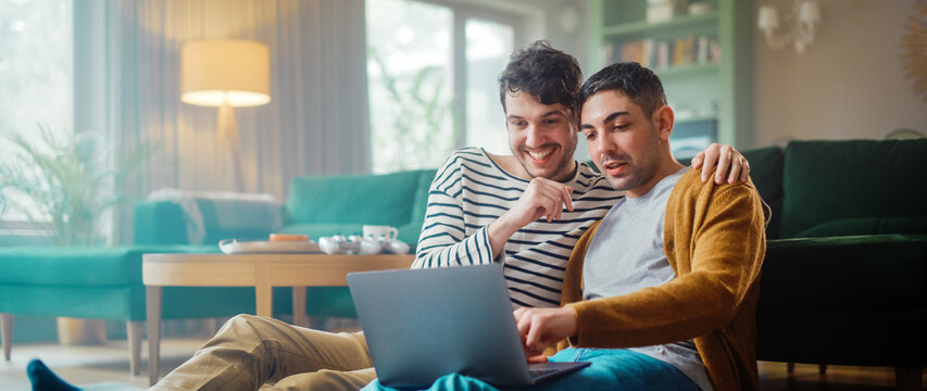 Handsome Gay Couple Using Laptop Computer, while Sitting on a Living Room Floor in Cozy Stylish Apartment. Adult Boyfriends Online Shopping on Internet, Watching Funny Videos on Streaming Service.