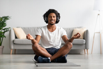 Meditation Concept. Calm Black Guy In Wireless Headphone Meditating At Home